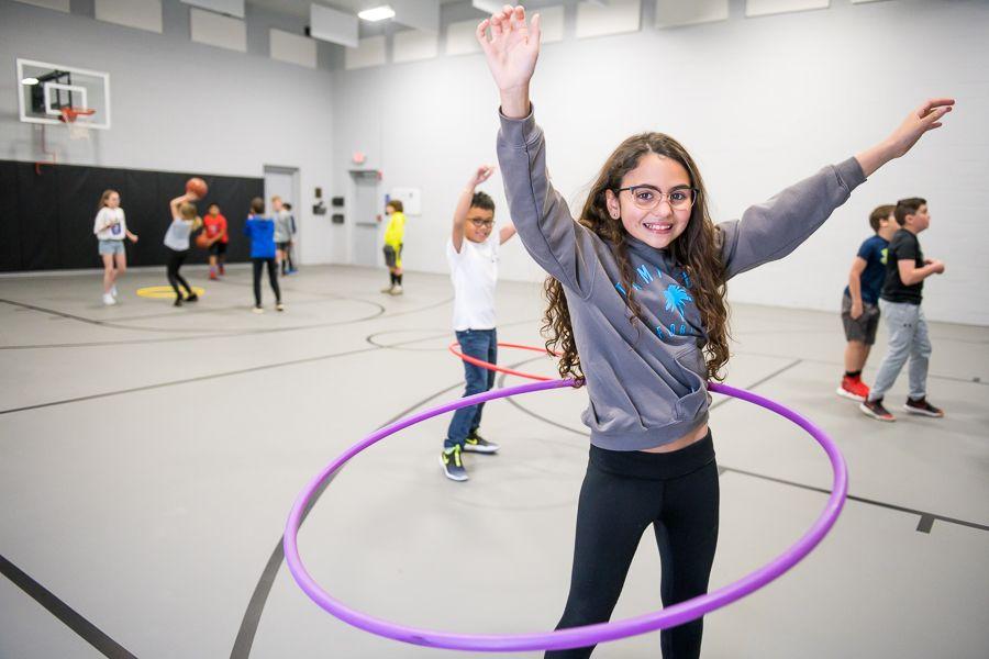 Girl Hula hooping in gym